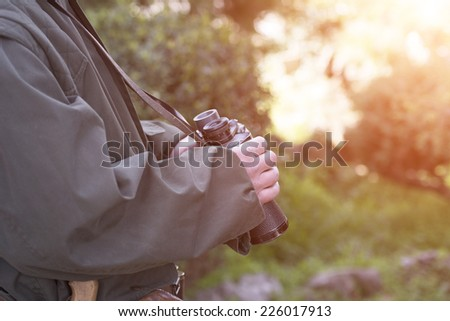 Hunter with a shotgun and pair of binoculars  - stock photo
