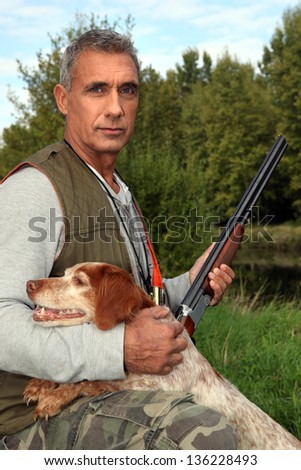 Hunter with a shotgun and spaniel - stock photo