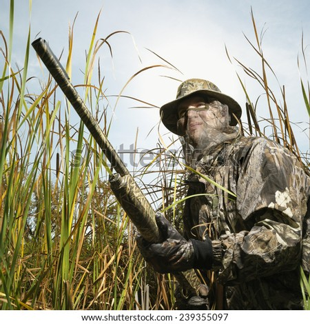 Hunter with Camouflage Face Mask and Gun - stock photo