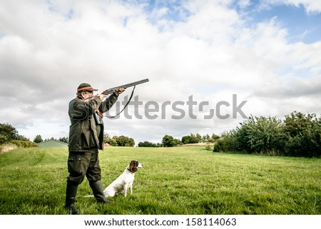 Hunter with dog aiming with his rifle - stock photo