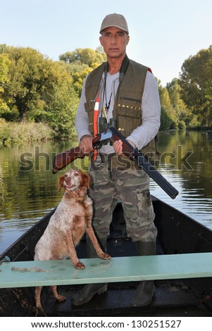 Hunter with dog on boat - stock photo