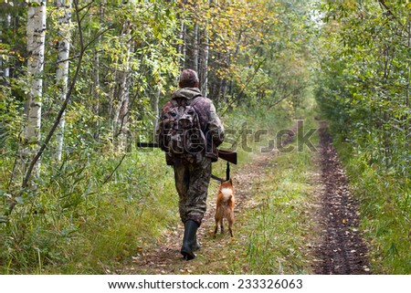 hunter with dog walking on the forest road  - stock photo