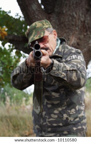Hunter with double barrel gun - stock photo