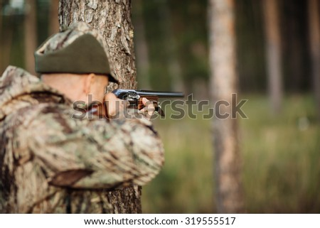 hunter with his rifle in forest, hunter holding a rifle and waiting for prey, hunter shooting - stock photo