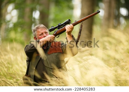 hunter with his rifle in spring forest, hunter holding a rifle and waiting for prey, hunter shooting and aiming - stock photo