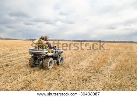 Hunters on quad bikes. - stock photo