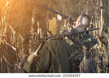 Hunters with his rifle in spring forest, hunter holding a rifle and waiting for prey, hunters shooting  - stock photo
