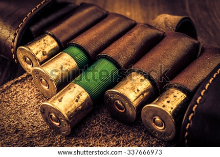 Hunting ammunition 12 gauge in leather bandolier on a wooden table. Focus on the cartridges, image vignetting and the yellow-blue toning - stock photo