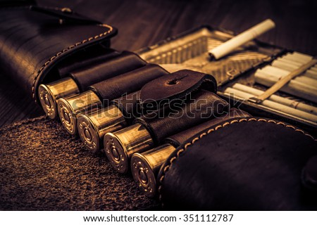 Hunting ammunition 12 gauge in leather bandolier with cigarette case and cigarettes on a wooden table. Focus on the cartridges, image vignetting and the yellow-blue toning - stock photo