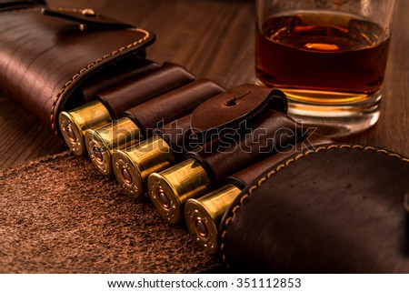 Hunting ammunition 12 gauge in leather bandolier with glass of whiskey on a wooden table. Focus on the cartridges - stock photo
