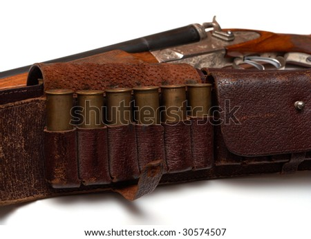 hunting belt with a cartridges and the rifle lying beside - stock photo