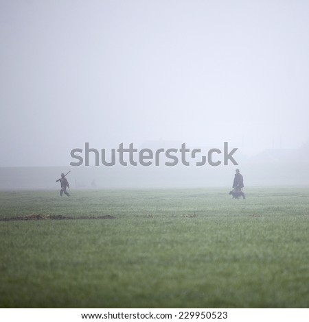 hunting party in meadow in holland under misty conditions - stock photo