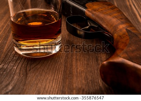Hunting rifle and glass of whiskey close-up. Focus on the glass of whiskey - stock photo