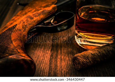 Hunting rifle and glass of whiskey with cuban cigar on the wooden table. Focus on the cuban cigar, image vignetting and the orange-blue toning - stock photo