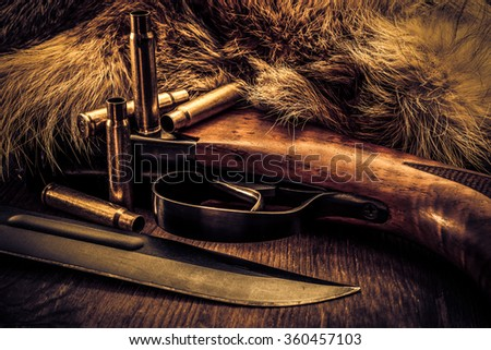 Hunting rifle with combat knife and empty shells lying next to the animal's fur produced. View close-up, image vignetting and the yellow-blue toning - stock photo