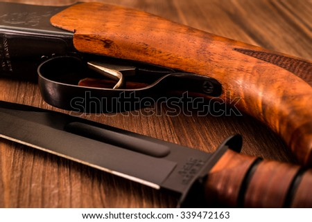 Hunting rifle with combat knife lying on a wooden table - stock photo