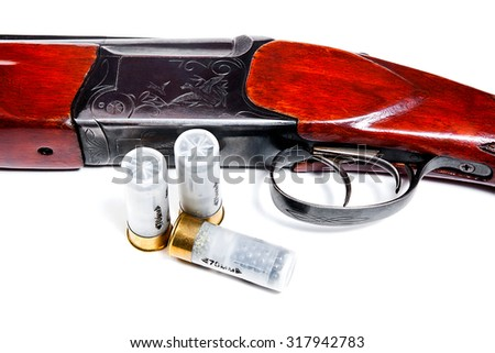 Hunting shotgun and ammunition on white background. Cartridges for hunting rifle. Close up view showing mechanism of hunting rifle. Isolated on white. - stock photo