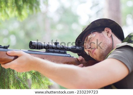 hunting, war, army and people concept - young soldier, ranger or hunter with gun aiming and shooting in forest - stock photo