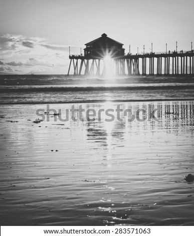 Huntington Beach Pier in Orange County California at Sunset with reflection processed in vintage black and white - stock photo