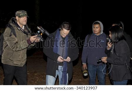 HUNTINGTON, NEW YORK, USA - NOVEMBER 14: Ron Yacovetti checks recording device during Brooklyn Paranormal Society's investigation of Mount Misery Road in Long Island.  Taken November 14, 2015 in NY.  - stock photo