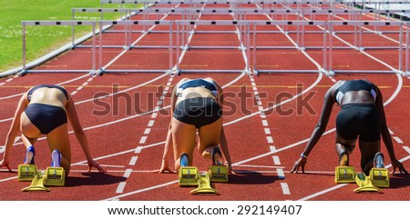 hurdle runners in start position - stock photo