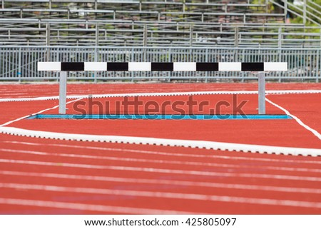 Hurdles on red running tracks - stock photo