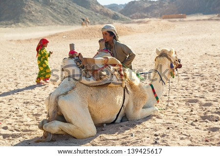 HURGHADA, EGYPT - APR 16: Unidentified bedouin child with camel resting on desert near Hurghada, April 16, 2013. Camel ride on the desert is one of the main local tourist attraction in Egypt. - stock photo