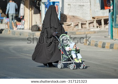 Hurghada, Egypt - November 7. 2006: Arabic mother in burqa conducts carriage with child - stock photo