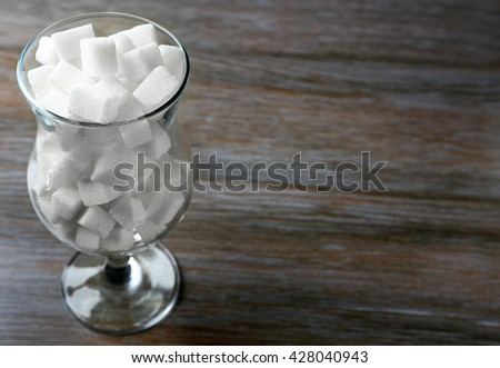 Hurricane glass with lump sugar on wooden table - stock photo