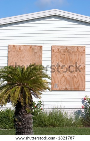 Hurricane protection plywood panels installed on tropical home - stock photo