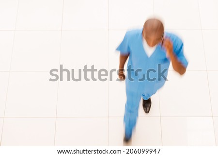 Hurrying surgeon . Top view of African doctor in blue uniform hurrying somewhere while talking on the mobile phone - stock photo