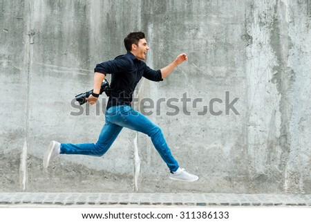 Hurrying to be first. Full length of young photographer running against a concrete wall - stock photo