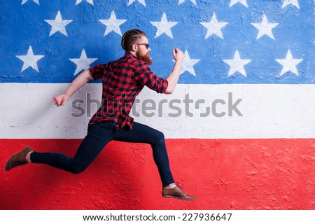 Hurrying to be in trend. Handsome young bearded man wearing sunglasses and running along American flag - stock photo