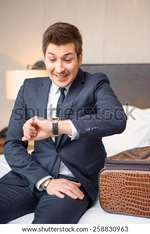 Hurrying up for the flight. Confident young businessman in suit and tie looking at his watch with emotional face expression while sitting on the bed in hotel room - stock photo