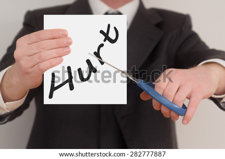 Hurt, man in suit cutting text on paper with scissors - stock photo