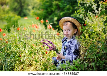 hurt the baby boy sitting in the grass with a bouquet of wildflowers. child in a straw hat sitting in the grass on a background of poppy field - stock photo