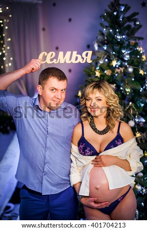 """husband and his pregnant wife holding a sign """"family"""". Christmas - stock photo"""