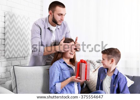 Husband and son giving a gift box to the wife - stock photo