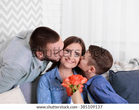 Husband and son giving roses to wife - stock photo
