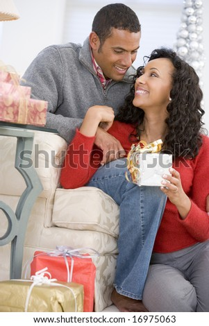 Husband And Wife Affectionately Exchanging Christmas Gifts - stock photo