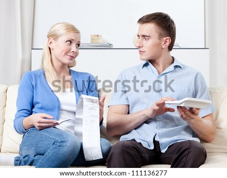 Husband and wife calculate the expenses sitting on the sofa - stock photo