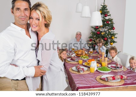 Husband and wife embracing beside the dinner table at christmas - stock photo