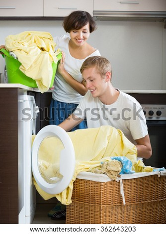 Husband and wife near washing machine with basket of linen - stock photo