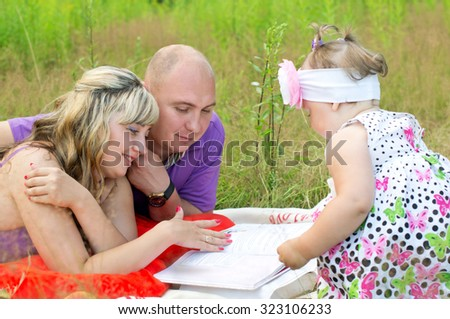 Husband and wife on the nature of the rest with a child - stock photo