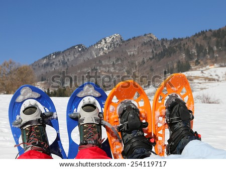 husband and wife on vacation with snowshoes in the mountain - stock photo