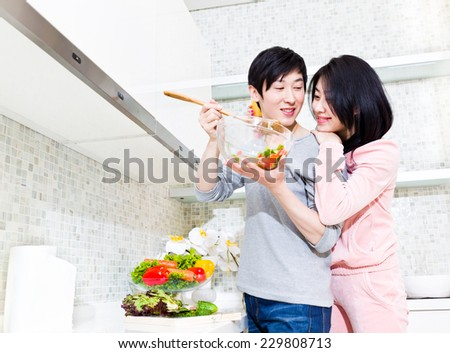 Husband and wife preparing food in the kitchen - stock photo