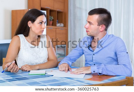 Husband and wife quarreling at banking statement indoors  - stock photo