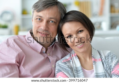 husband and wife spend time together on the couch - stock photo