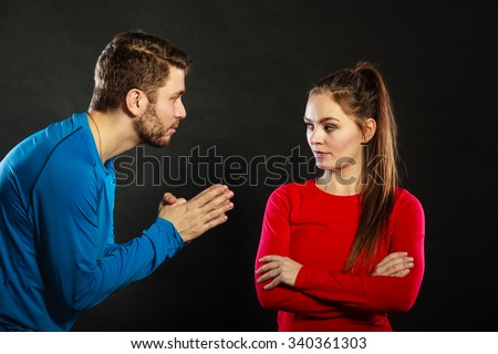 Husband apologizing upset angry wife. Man asking woman for forgivness. Boyfriend trying to convince girlfriend. Conflicted couple in studio on black. Relationship problem. - stock photo