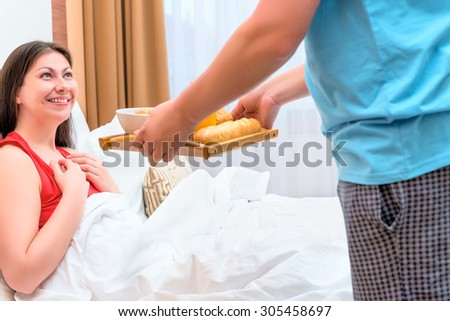 husband brought his wife breakfast in bed - stock photo